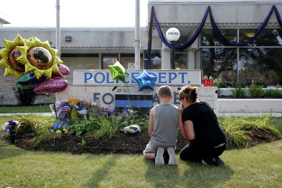 A passerby places an American flag at a memorial in front of the Fox Lake Police Department in Fox Lake on Wednesday, Sept. 2, 2015. Gliniewicz was shot and killed Tuesday while pursuing a group of suspicious men. Police are searching for a second day to locate three suspects in the killing.  (Jose M. Osorio/Chicago Tribune via AP) ORG XMIT: ILCHT102 Photo: Jose M. Osorio / Chicago Tribune