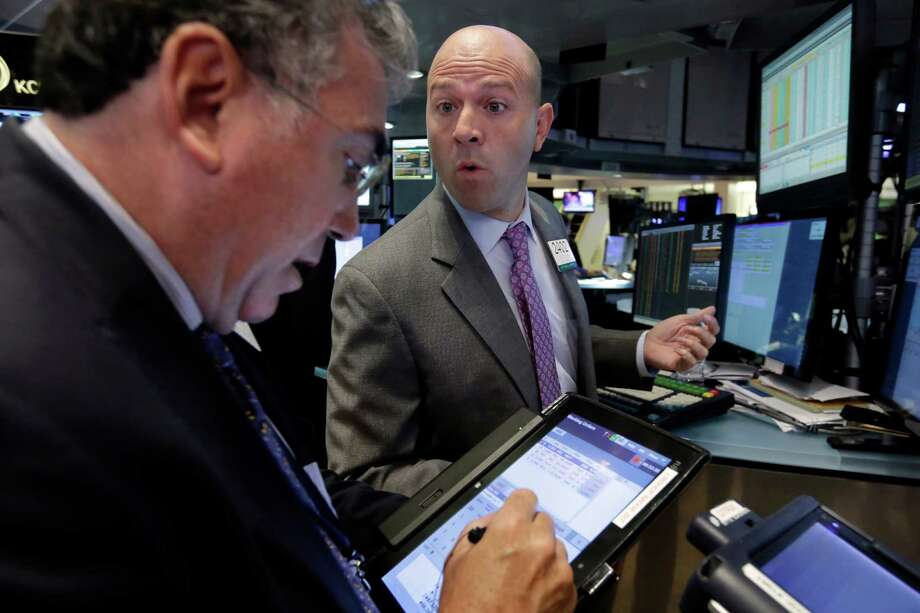 Specialist Jay Woods, right, works with trader John Bishop on the floor of the New York Stock Exchange, Wednesday, Sept. 2, 2015. U.S. and global stock markets were recovering in early morning trading Wednesday after a sharp sell-off a day earlier. Still, investors remain on edge after a plunge in stocks Tuesday that was triggered by reports showing slowing growth in China. (AP Photo/Richard Drew) Photo: Richard Drew, STF / AP