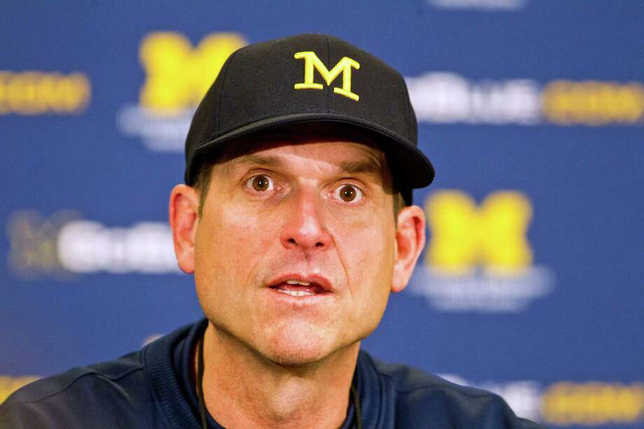 FILE - In this April 4, 2015, file photo, Michigan head coach Jim Harbaugh answers questions during a press conference after their spring NCAA college football game in Ann Arbor, Mich. The Jim Harbaugh hype train has reached its destination in Salt Lake City. After eight months of living in the spotlight as college football's latest rock star _ and putting Michigan in the national conversation for the first time in years _ the Wolverines new coach is ready to move past the glitz and get gritty on the football field. (AP Photo/Tony Ding) File ORG XMIT: NY167 Photo: Tony Ding / FR143848 AP