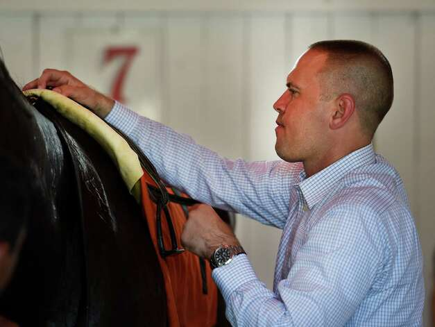 Trainer Chad Brown saddles a horse for the 8th race on the card Wednesday afternoon Sept. 2, 2015 at the Saratoga Race Course in Saratoga Springs, N.Y.    (Skip Dickstein/Times Union) Photo: SKIP DICKSTEIN
