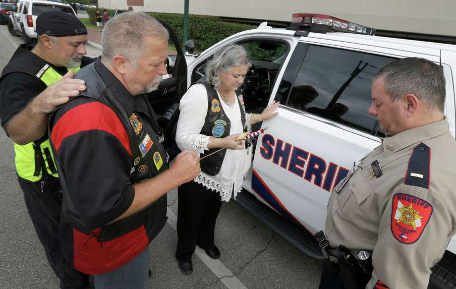 Members of the Christian Motorcyclists Association Ralph Robson, left, Eric Story, and his wife, Cheri Story, bless the patrol vehicle of Montgomery County Sheriff's Lt. David Dottei, right, after a service for law enforcement at First Baptist Church of Conroe, 600 North Main St.,  Wednesday, Sept. 2, 2015, in Conroe. Photo: Melissa Phillip, Houston Chronicle / © 2015 Houston Chronicle