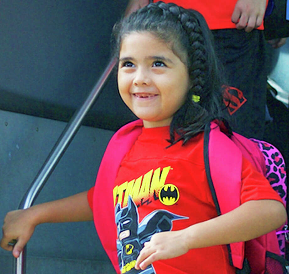 Eager to learn  Eliana Jimenez is all smiles when greeted by a staff member as she gets off the bus on the first day at Hill and Plain School, Aug. 24, 2015.  More than 4,000 students opened the 2015-16 school year last week in New Milford public schools. For more photos, see Page S16 and visit www.newmilfordspectrum.com. Photo: Trish Haldin / Trish Haldin / The News-Times Freelance
