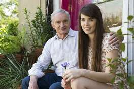 Portrait of young woman and grandfather on back door steps
