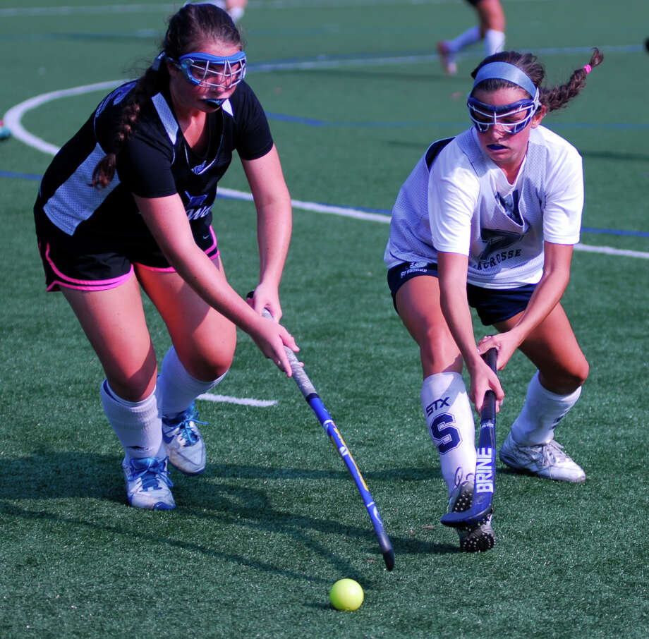 Staples defender Megan Johnson, right, battles with a Darien player during a field hockey scrimmage this week. Photo: / Ryan Lacey /Staff Photo / Westport News Contributed