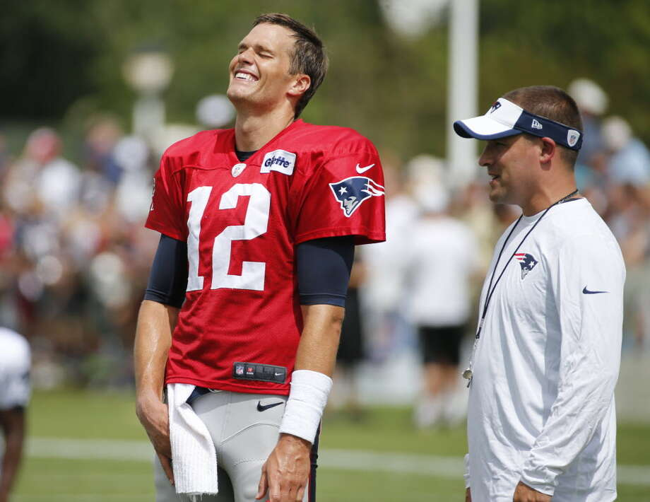 New England Patriot quarterback Tom Brady (12) shares a laugh with offensive coordinator Josh McDaniels during a joint practice between the Patriots and New Orleans Saints at the Saint's NFL football training camp, Wednesday, Aug.19, 2015, in White Sulphur Springs, W.Va. (AP Photo/Steve Helber)