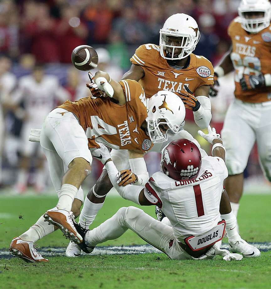 Arkansas wide receiver Jared Cornelius (1) loses control of the ball as he was tackled by Texas defensive back Dylan Haines (44) and safety Mykkele Thompson (2) during the first quarter of the AdvoCare V100 Texas Bowl at NRG Stadium on Monday, Dec. 29, 2014, in Houston. ( Brett Coomer / Houston Chronicle ) Photo: Brett Coomer, Staff / © 2014 Houston Chronicle