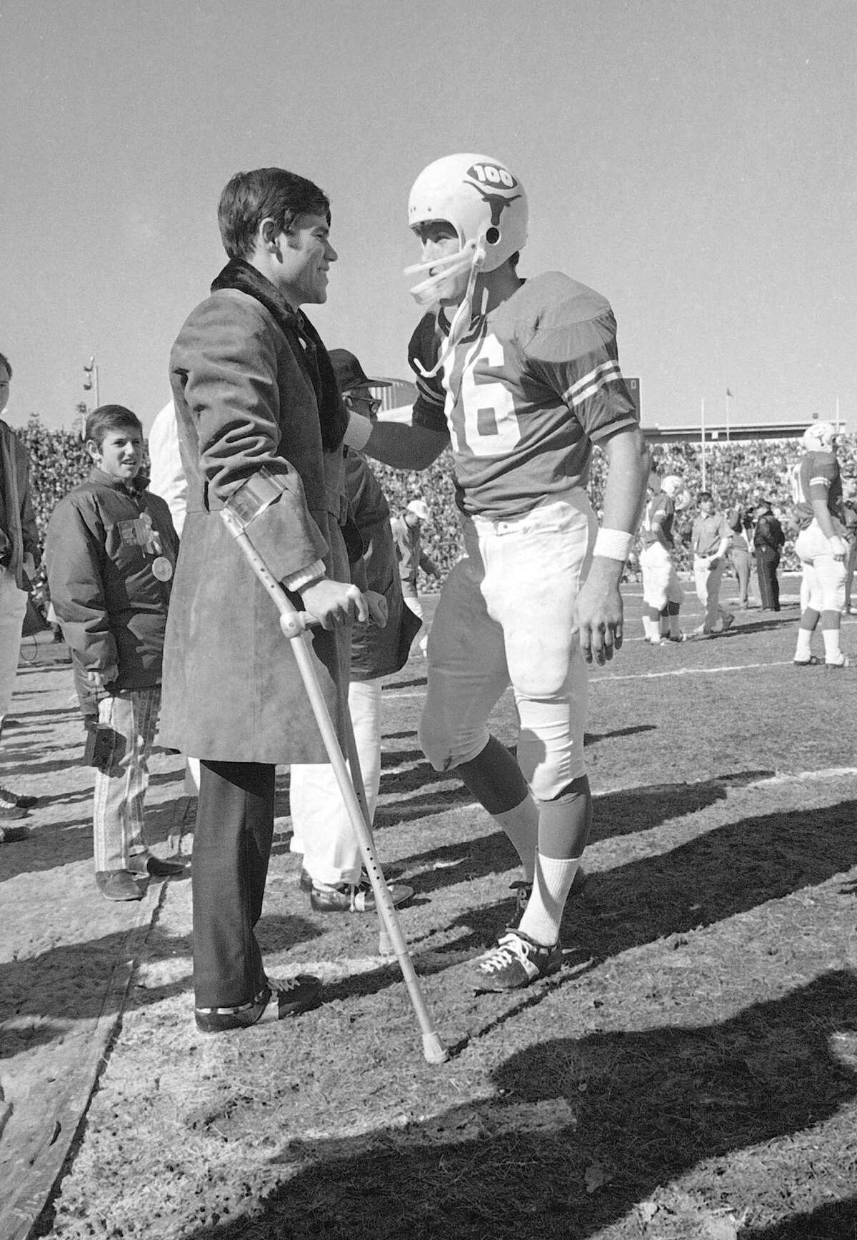Freddie Steinmark, University of Texas football star who lost his left leg to cancer, chats with Texas quarterback James Street on the sidelines before the start of the Notre Dame-Texas Cotton Bowl game in Dallas, Jan. 1, 1970. Steinmark left the hospital in Houston to attend the game. (AP Photo)