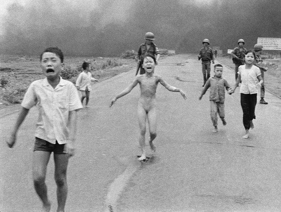"In this June 8, 1972, file photo taken by Huynh Cong ""Nick"" Ut, South Vietnamese forces follow behind terrified children, including 9-year-old Kim Phuc (center) as they run down Route 1 near Trang Bang after an aerial napalm attack on suspected Viet Cong hiding places. Photo: Nick Ut, Associated Press"