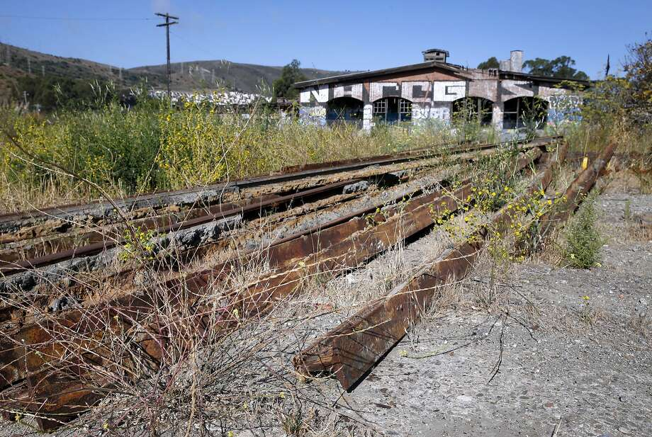 Rusty sections of rail are lined up near the crumbling Bayshore Roundhouse, at what was once a Southern Pacific railroad yard, on open space land between Bayshore Boulevard and Highway 101 in Brisbane, Calif. on Thursday, Sept. 3, 2015. The historic roundhouse will be restored as part of the Baylands mixed-use development project which is planned for the 660-acre site. Photo: Paul Chinn, The Chronicle
