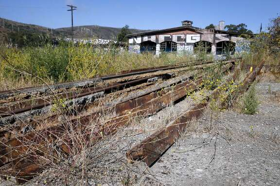 Rusty sections of rail are lined up near the crumbling Bayshore Roundhouse, at what was once a Southern Pacific railroad yard, on open space land between Bayshore Boulevard and Highway 101 in Brisbane, Calif. on Thursday, Sept. 3, 2015. The historic roundhouse will be restored as part of the Baylands mixed-use development project which is planned for the 660-acre site.