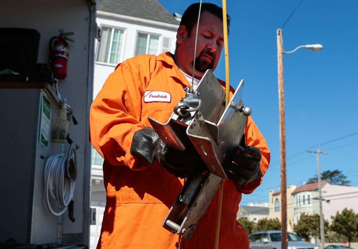 PUC worker Francisco Lastra lowers an apparatus that helps protect cables as they raise the cameras used to inspect sewage lines.