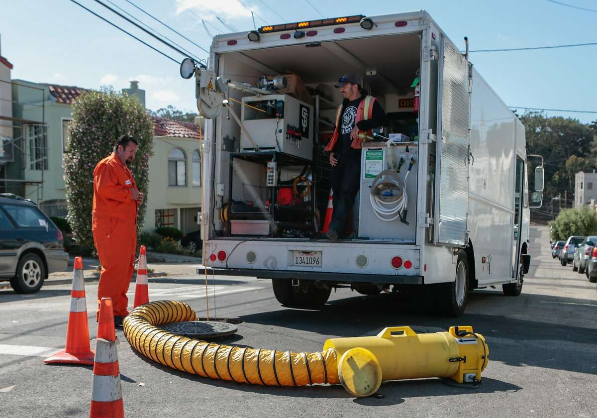 (L-R) Public Utility Commission employees Francisco Lastra and Andrew Wayne inspect a newly installed sewage line at Cabrillo Street and 29th Avenue in San Francisco.