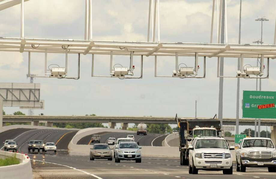 Drivers pass under the Toll Tag readers on the new Tomball Tollway. More drivers are using the $73 million roadway each month. Photo: David Hopper, Freelance / freelance