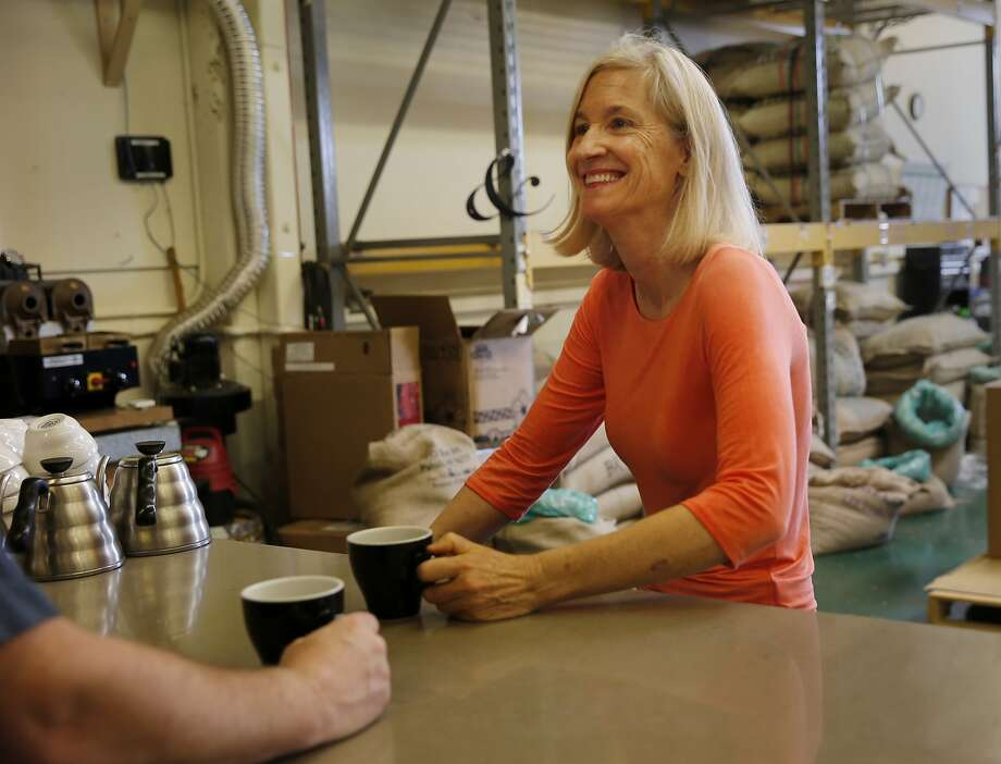 Equator Coffee co-founder Brooke McDonell enjoys a cup of her fair-trade coffee with a colleague at the company's 