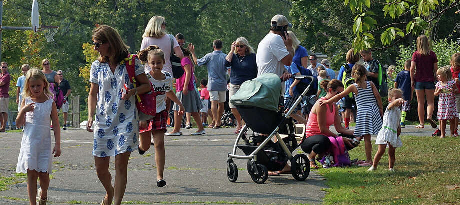 "Parents are reunited with their children Thursday afternoon after the first day of school at Sherman School, which has a large contingent of ""walkers."" Photo: Genevieve Reilly / Fairfield Citizen / Fairfield Citizen"