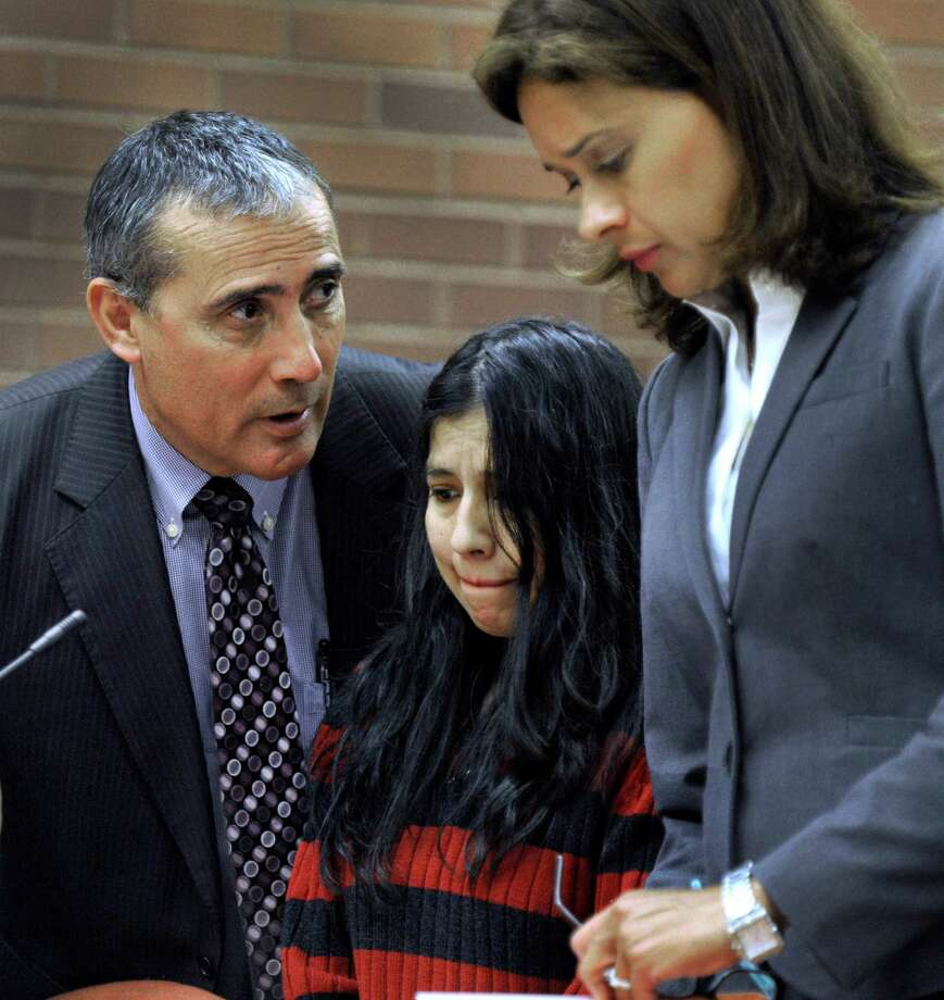 Lidia Quilligana, 31, the police said was caught on camera burning the hands and leg of a 3-year-old girl she was babysitting, pleaded not guilty Wednesday, April 22, 2015. Quilligana, center, appeared in State Superior Court in Danbury, Conn. and was aided by interpreter Javier Lillo and represented by her attorney Jennifer Tunnard. Photo: Carol Kaliff / Carol Kaliff / The News-Times