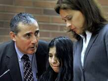 Lidia Quilligana, 31, the police said was caught on camera burning the hands and leg of a 3-year-old girl she was babysitting, pleaded not guilty Wednesday, April 22, 2015. Quilligana, center, appeared in State Superior Court in Danbury, Conn. and was aided by interpreter Javier Lillo and represented by her attorney Jennifer Tunnard.