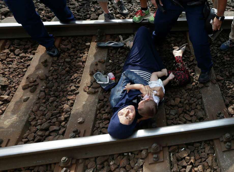 A migrant lies on the track with a baby as she is detained  in Bicske, Hungary, Thursday, Sept. 3, 2015. Over 150,000 migrants have reached Hungary this year, most coming through the southern border with Serbia. Many apply for asylum but quickly try to leave for richer EU countries. (AP Photo/Petr David Josek) Photo: Petr David Josek, STF / AP