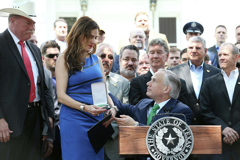 "Taya Kyle, the widow of Chris Kyle, accepts the Legislative Medal of Honor from Texas Gov. Greg Abbott as she stands with veterans she asked up to the podium during a ceremony on the Governor's Mansion front lawn, Wednesday, Aug. 26, 2015. Abbott presented the Texas Legislative Medal of Honor to representatives of Chief Petty Officer Chris Kyle, the slain ""American Sniper,"" and Lt. Col. Ed Dyess. The Texas Legislative Medal of Honor is the highest military decoration that can be awarded to a member of the state or federal military forces by the State of Texas. (Ralph Barrera/Austin American-Statesman via AP) Photo: Ralph Barrera, MBO / Austin American-Statesman"