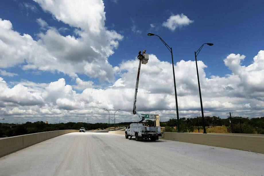 A electrician on a lift works on a street lamp on the nearly completed Wurzbach Parkway over U.S. 281 on Thursday. Photo: Kin Man Hui /San Antonio Express-News / ©2015 San Antonio Express-News