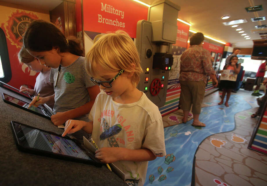 Fourth-grader J.C. Yaeger, 9 (center), works with a tablet computer in the History in Motion RV, which came to the Monte Vista Montessori School. Photo: Photos By John Davenport / San Antonio Express-News / ©San Antonio Express-News/John Davenport