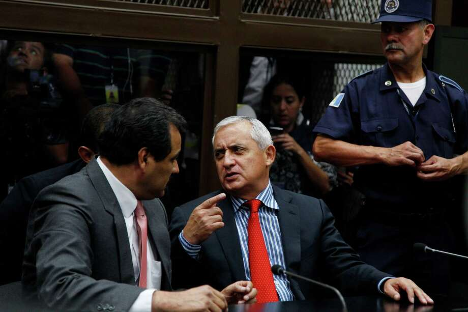Guatemala's former President Otto Perez Molina, right, talks to his lawyer Cesar Calderon as he sits in court to face corruption charges in Guatemala City on Thursday. Perez Molina was under orders not to leave the country and Tuesday the congress lifted his immunity from prosecution. Photo: Luis Soto, STR / AP