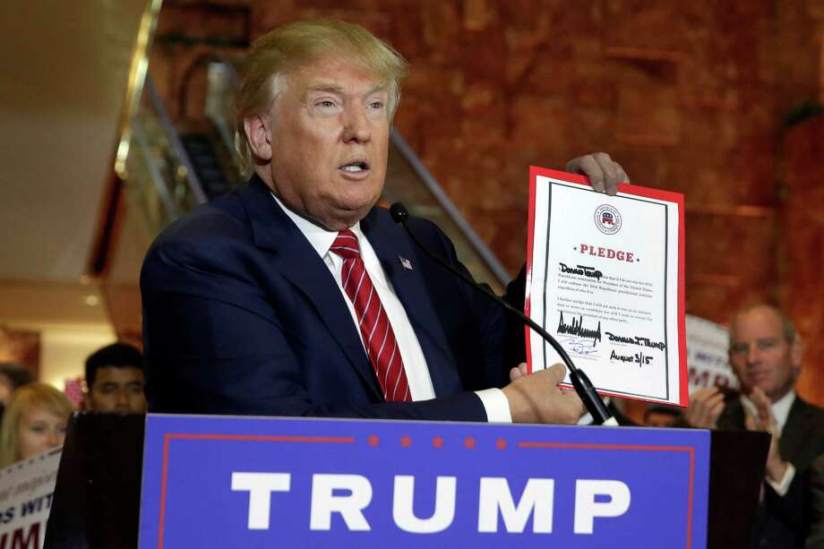 Republican presidential candidate Donald Trump holds a signed pledge during a news conference in Trump Tower, Thursday, Sept. 3, 2015 in New York. Trump ruled out the prospect of a third-party White House bid and vowed to support the Republican Party's nominee, whoever it may be. (AP Photo/Richard Drew) ORG XMIT: NYRD108 Photo: Richard Drew / AP