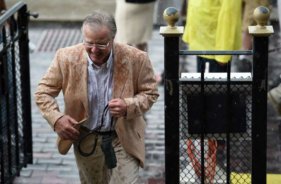 Trainer Bill Mott runs for cover from a thunderstorm after his charge Harmonize won the 11th running of The P. G. Johnson Thursday afternoon Sept. 3, 2015 at the Saratoga Race Course in Saratoga Springs, N.Y.    (Skip Dickstein/Times Union) Photo: SKIP DICKSTEIN