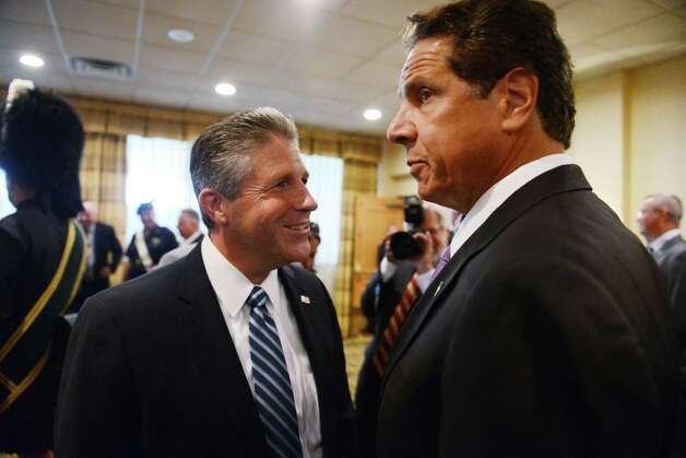 Patrick Lynch president of the New York City Patrolmen's Benevolent Association, left, speaks to Gov. Andrew Cuomo during the New York City PBA's annual convention Thursday, Aug. 3, 2015, where Gov. Cuomo spoke to members at the Holiday Inn in Colonie, N.Y. Gov. Cuomo was awarded with the association's Man of the Year award. (Will Waldron/Times Union) Photo: Will Waldron / 00033226A
