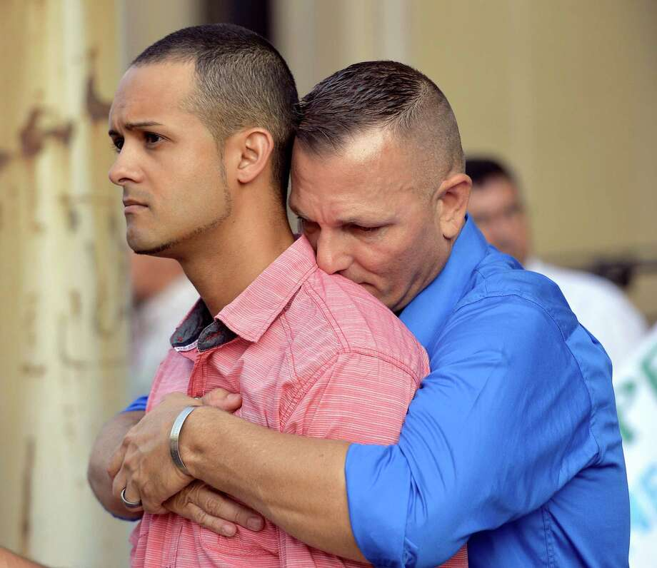 Jonathan Beebe-Franqui, left, and his husband Dwayne D. Beebe-Franqui embrace as they wait for the arrival of Rowan County Clerk Kim Davis at the Carl D. Perkins Federal Building in Ashland, Ky., Thursday, Sept. 3, 2015. Davis has been ordered to appear in Federal Court to explain why she is refusing to issue marriage licenses despite a federal order to do so. (AP Photo/Timothy D. Easley) Photo: Timothy D. Easley, FRE / Associated Press / FR43398 AP