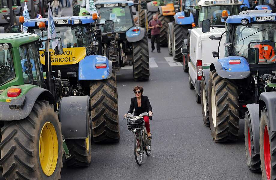 A woman rides her bike between tractors as angry farmers demonstrate in Paris, Thursday, Sept. 3, 2015. Hundreds of tractors were descending on Paris on Thursday in a boisterous protest by farmers blocking highways to express their anger over falling French food prices and high taxes. They are protesting increasingly slim margins they blame on cheap imports and high payroll charges.  Photo: Christophe Ena, Associated Press