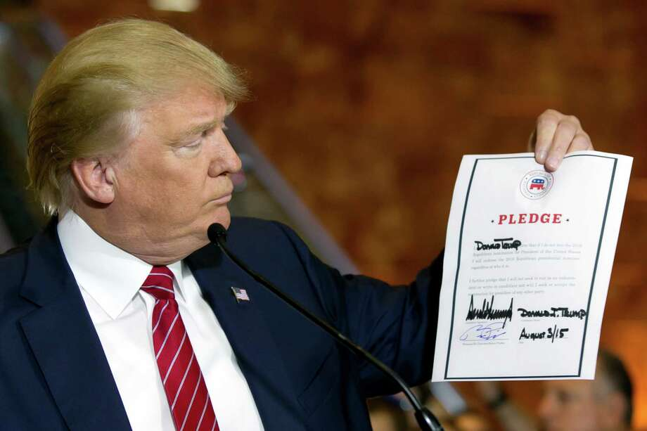 Republican presidential candidate Donald Trump looks at a signed pledge during a news conference in Trump Tower, Thursday, Sept. 3, 2015 in New York. Trump ruled out the prospect of a third-party White House bid and vowed to support the Republican Party's nominee, whoever it may be. (AP Photo/Richard Drew) Photo: Richard Drew, STF / Associated Press / AP