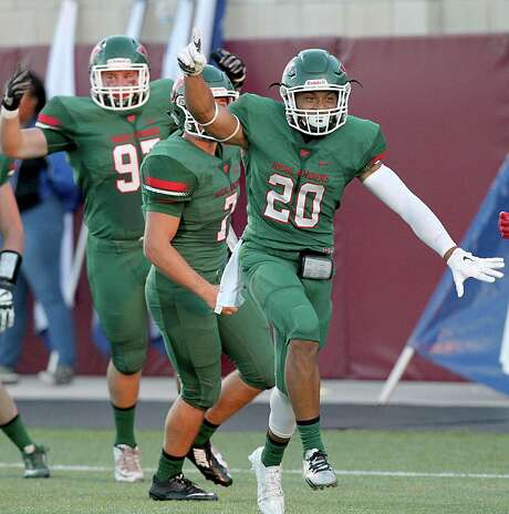 The Woodlands' Antoine Winfield Jr., right, celebrates turning a fumble recovery into a 32-yard return for a touchdown. He later recovered another fumble. Photo: Thomas B. Shea / © 2015 Thomas B. Shea