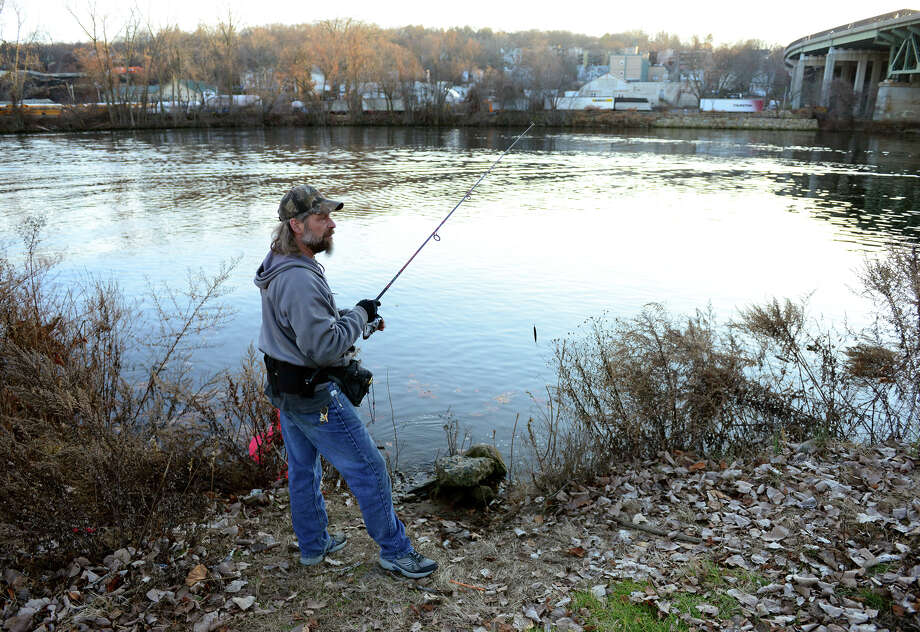 John Machowski Jr. spends some time fishing along the bank of the Housatonic River at O'Sullivan's Island Recreation Park in Derby, Conn., on Friday Dec. 26, 2014. Photo: Christian Abraham / Christian Abraham / Connecticut Post