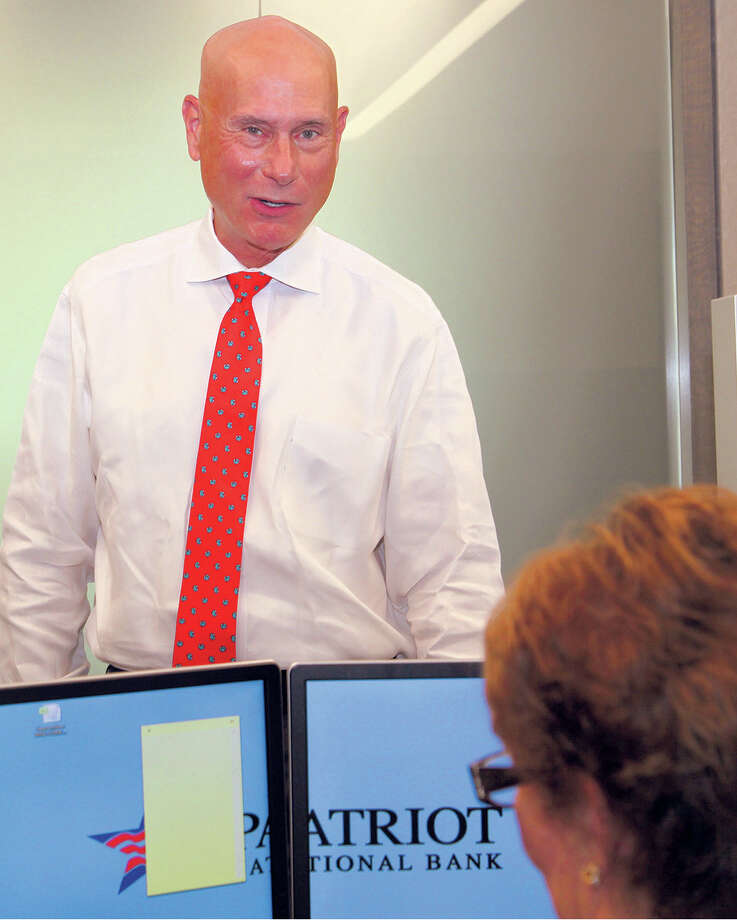 Patriot National Bank CEO Ken Neilson talks with an employee in his Stamford office. Photo: Danielle Brody /Contributed Photo / Stamford Advocate