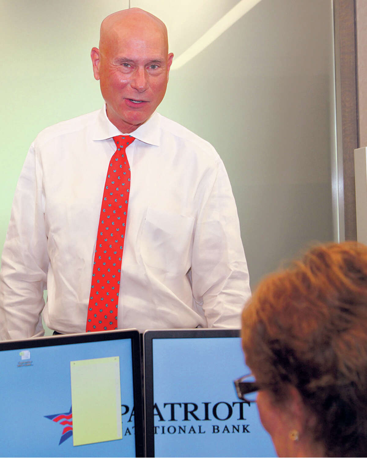 Patriot National Bank CEO Ken Neilson talks with an employee in his Stamford office.