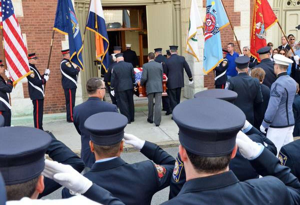 Firefighters salute as the coffin of retired Albany Fire Chief Robert Forezzi Sr. is carried into Historic St. Mary's Church in Albany on Friday, Sept. 4, 2015. (John Carl D'Annibale/Times Union)