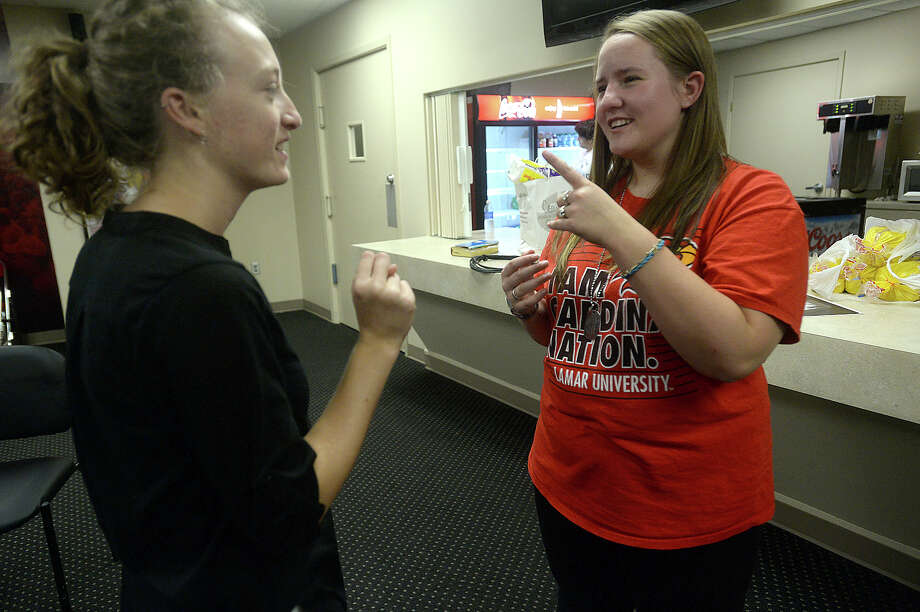 Allie Hayes (right), a junior at Lamar University majoring in the teaching track of American Sign Language (ASL), talks with Jessica Romine, who acts as a student interpreter at Beaumont's Campus Church Wednesday services. The weekly group meets at the Montagne Center, offering worship time for those who are hearing - impaired as well as others studying ASL. Allie was born profoundly deaf, and received her first cochlear implant when she was 20-months-old. At 13, she chose to get a second implant, and though it significantly aids in her ability to hear, says there are still challenges.  Photo taken Wednesday, September 2, 2015 Photo by Kim Brent Photo: Kim Brent / Beaumont Enterprise