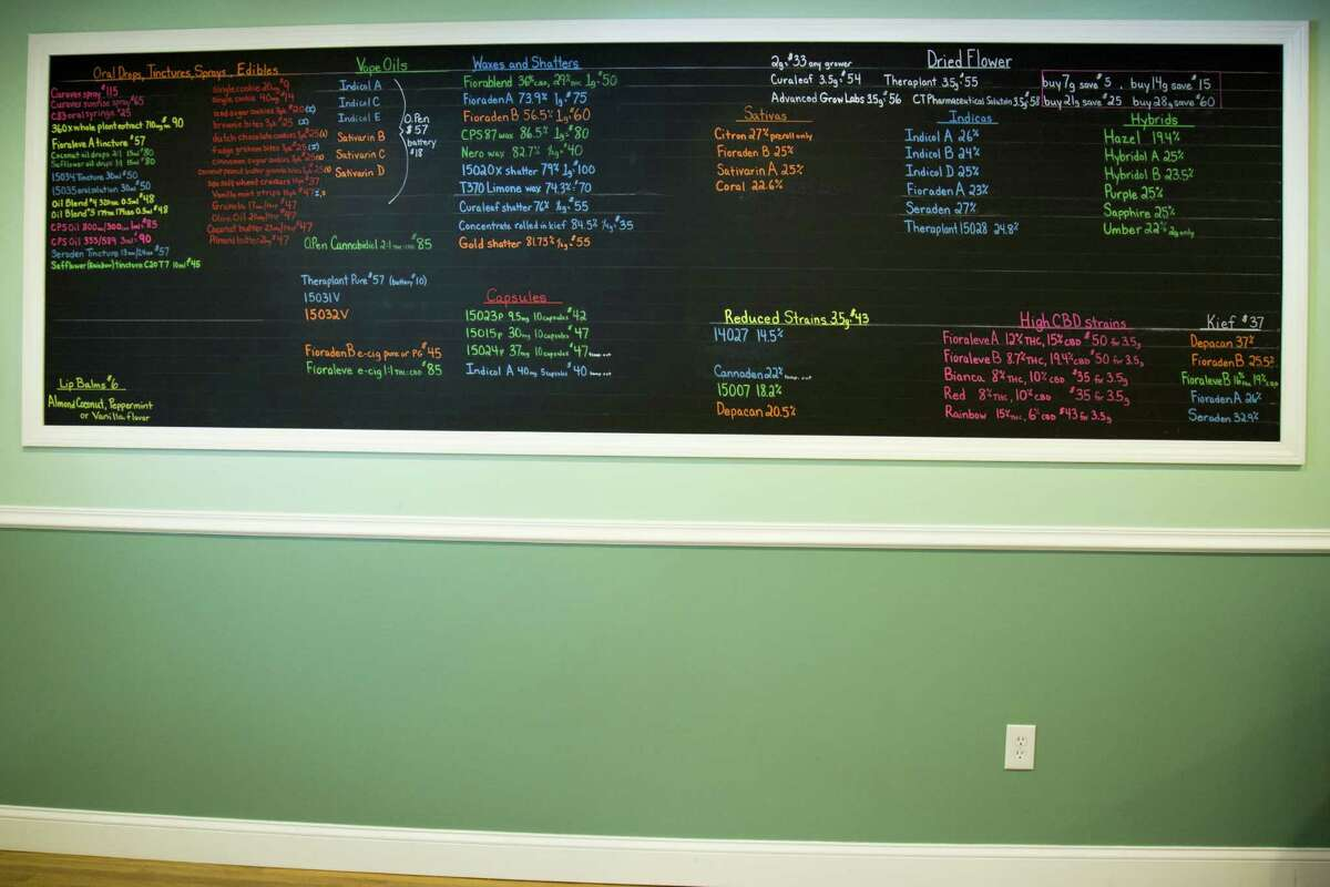 A board displays available strains and medical marijuana-infused products at Thames Valley Alternative Relief. In Connecticut, dispensaries may not display names like