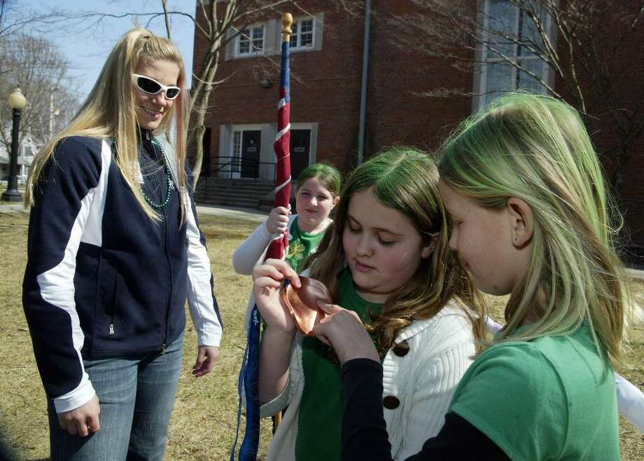 (L-R) Erin Pac, who won a silver medal in bobsled at the Vancouver Olympics shows her medal to Theresa Piscitelli, Carly Malesky and Veronic Piscitelli, Sunday, March 21, 2010. Pas was riding in the Milford St. Patrick's  Day Parade. Photo: Phil Noel / Connecticut Post