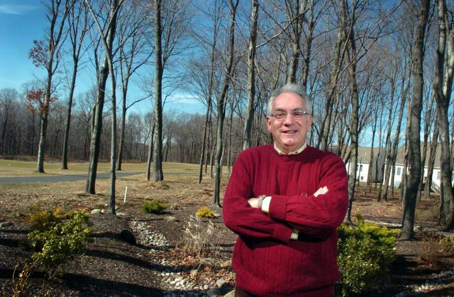 Peter Bunzl stands in the backyard of his Oxford Greens home, overlooking the 14th hole of the golf course.  Bunzl moved from Westchester County a few years ago with his wife who fell in love with the atmosphere in Oxford. Photo: Autumn Driscoll / Connecticut Post