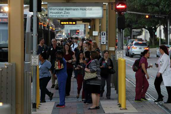 Commuters bustle Thursday at a light rail stop in the Texas Medical Center.