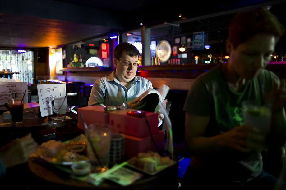 "Minty Monday regular Mike Frentz looks through the karaoke song book at The Mint July 20, 2015 in San Francisco, Calif. ""Music is life, karaoke is oxygen,"" said Frentz, who has been frequenting Minty Mondays for nearly two years. Photo: Erin Brethauer, The Chronicle"