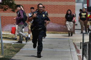 A police officer runs down a sidewalk Friday September 4, 2015 at Edison High School where the San Antonio Fire Department was called about noon. San Antonio Independent School District spokesperson Leslie Price said a junior at the school somehow became locked in a safe in the school's ROTC area. Price said firefighters have drilled holes in the combination safe and that the student's parents have been notified.