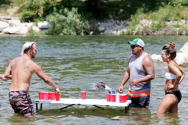 Trying to stay cool people play beer pong in the Guadalupe River at the Faust Street Bridge Sunday July 26, 2015 in New Braunfels , Tx.