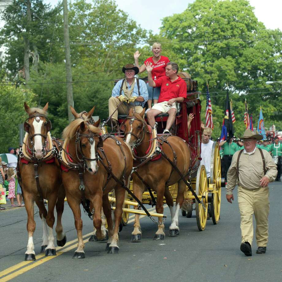 Horses pull a coach of riders down Main Street in Newtown's 53rd annual Labor Day Parade last year. Photo: H John Voorhees III / H John Voorhees III / The News-Times Freelance