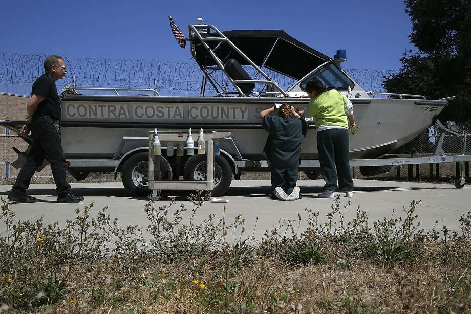 Inmates (right) decal a costa county sheriff vehicle at the West County Detention Jail Facility in Richmond, Calif., on Thursday, September 3, 2015. Photo: Liz Hafalia, The Chronicle