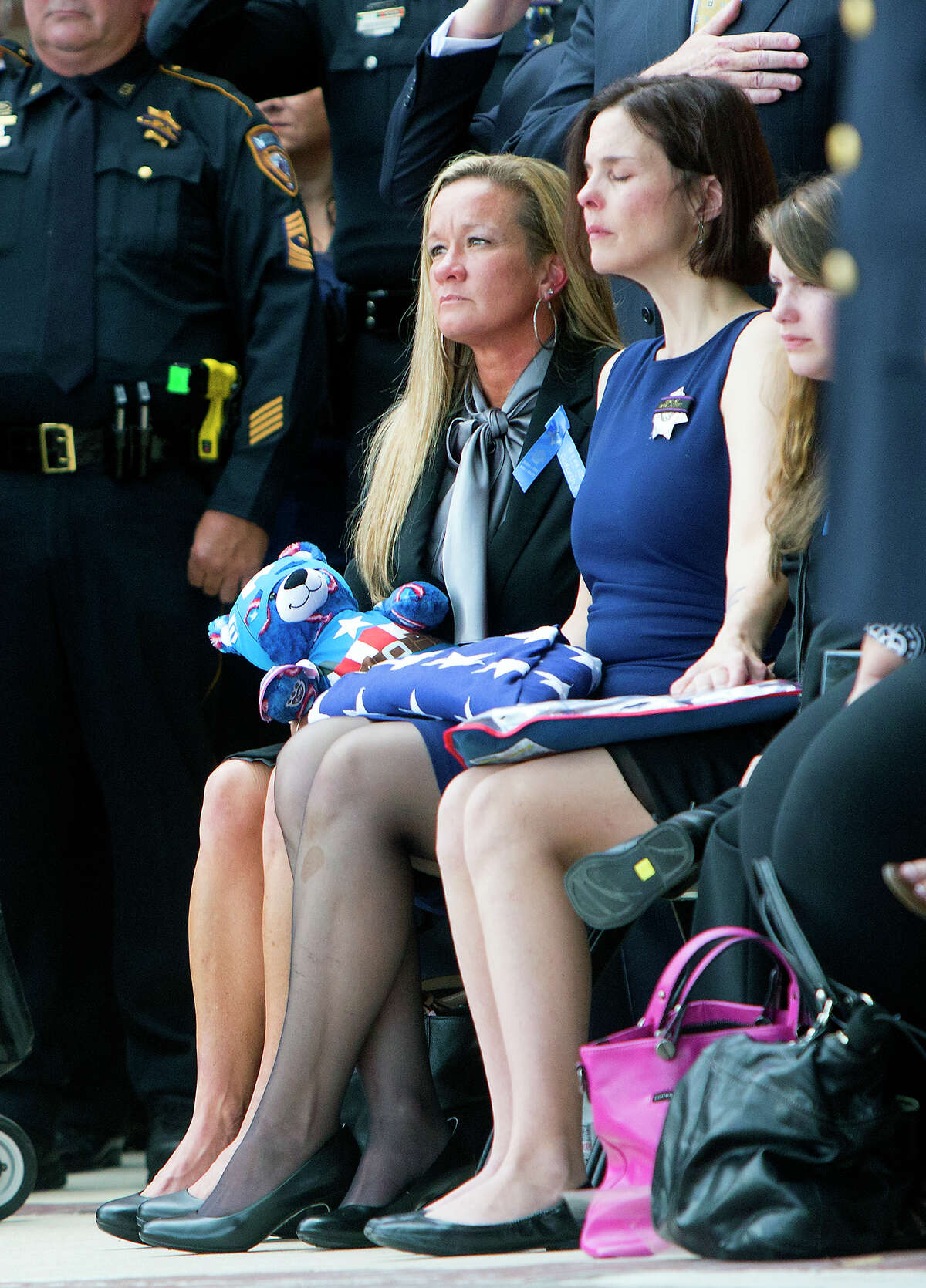 Harris County Sheriff's Deputy Darren Goforth's wife, Kathleen Goforth, right, reacts during his funeral service at Second Baptist Church, Friday, Sept. 4, 2015, in Houston. Goforth was shot to death a week ago at a service station as he pumped gas into his police cruiser. Shannon Miles, 30, stands charged with capital murder in Goforth's death.