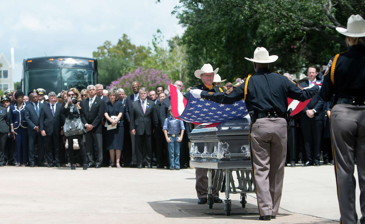 The Harris County Sheriff's Department prepares to fold the flag draped over the casket of Deputy Darren Goforth during his funeral service at Second Baptist Church, Friday, Sept. 4, 2015, in Houston. Goforth was shot to death a week ago at a service station as he pumped gas into his police cruiser. Shannon Miles, 30, stands charged with capital murder in Goforth's death.