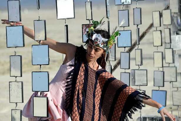 Danielle Petooie of Barzel walks through an art piece at Burning Man on Wednesday, Sept. 2, 2015, in Gerlach, Nev. The Burning Man's theme is Carnival of Mirrors. (Andy Barron /The Reno Gazette-Journal via AP) NO SALES; NEVADA APPEAL OUT; SOUTH RENO WEEKLY OUT; MANDATORY CREDIT